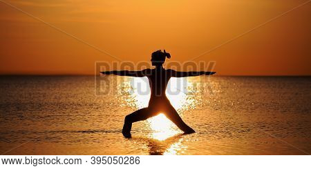 Silhouette Of A Slender Girl Practicing Yoga At The Background Of A Red-orange Sunset On The Sea (oc
