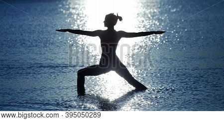 Silhouette Of A Slender Girl Practicing Yoga In The Water. Background Of A Blue Sea (ocean, Lake) An