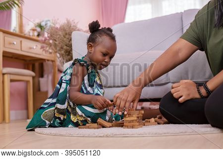 African Americans' Mother And Daughter Playing Block Wooden Games Together In Living Room. Black Peo