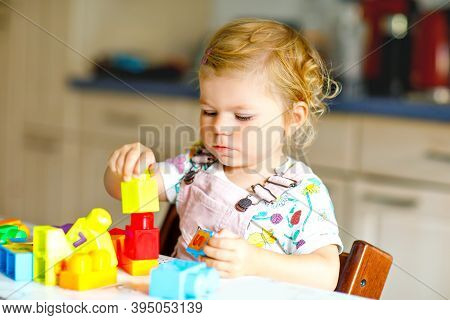 Adorable Toddler Girl Playing With Educational Toys In Nursery. Happy Healthy Child Having Fun With