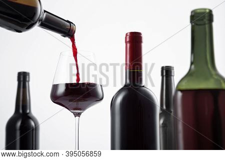 Bottle Of Red Wine Poured Into The Wine Glass, And Variety Of Wine Bottles With Selective Focus On
