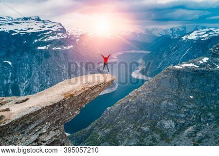 Norway, A woman Jump on the mountain's cliff edge of Trolltunga throning over Ringedalsvatnet  watching the sunset and snowy Norwegian mountains near Odda, Rogaland, Norway