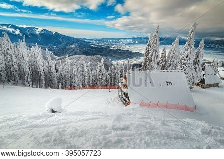 Snow Covered Winter Scenery And Ski Slopes In The Pine Forest. Cozy Snowy Alpine Chalets Near Fantas