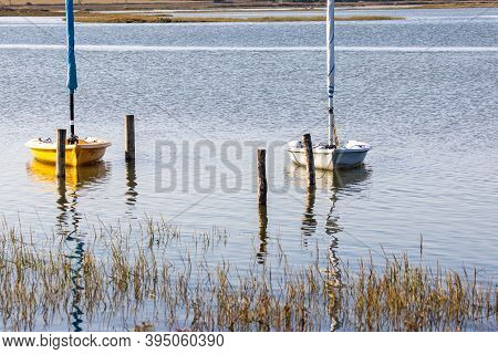 Wo Small Dinghy Sailing Boats In River By Bank Of Reeds With Mooring Posts, River In Background