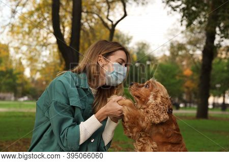 Woman In Protective Mask With English Cocker Spaniel In Park. Walking Dog During Covid-19 Pandemic