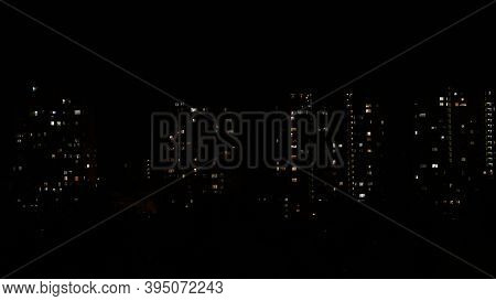Night City View With Lights In Windows Of Multistory Buildings In Darkness. Blur Lights Of Residenti