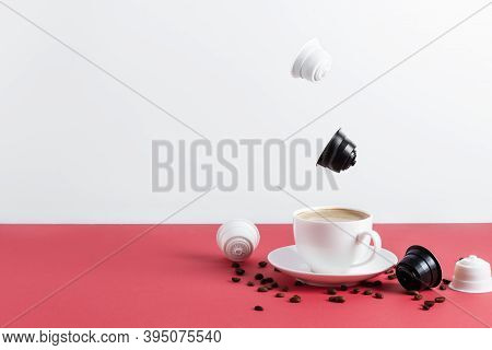 Espresso Coffee Capsules And Roasted Coffee Beans Levitating Above Coffee Cup. Cappuccino Made From
