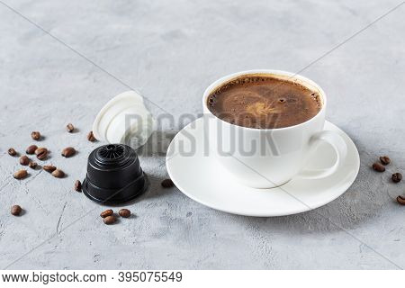 Espresso Coffee Capsules And Coffee Cup On Grey Background. Latte Made From Coffee And Milk Capsules