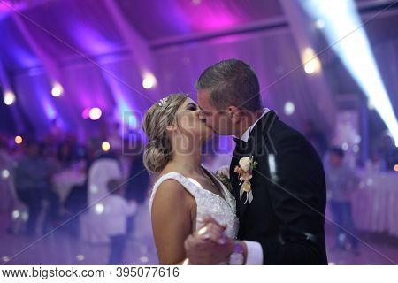 Groom Holds Bride Carefully Dancing In The Restaurant. First Dance Bride. Happy Bride And Groom And