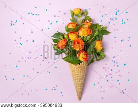 Fresh Yellow-orange Roses In A Waffle Cone On A Pink Background With Small Stars. Copy Space, Flat L