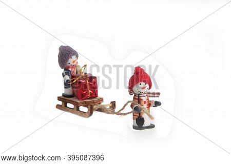 Snowmen With Sledge Loaded With Bright Christmas Gift Isolated On White Background. Winter Holiday C