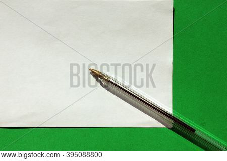 A Ballpoint Pen For Writing On A Green Background. View From Above. The Handle Is A White Case. Hand