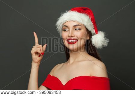 Christmas Woman In Santa Hat Pointing Up On Black Background. Christmas Holiday And New Year Party