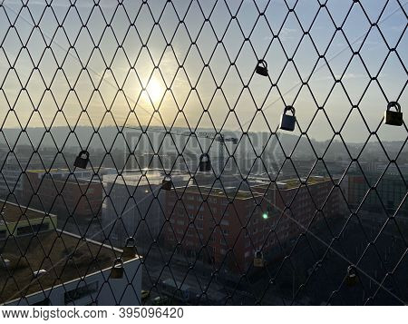 A Lock Is Attached To A Grille. The Sun Begins To Set In The Background. Photographed In Zurich
