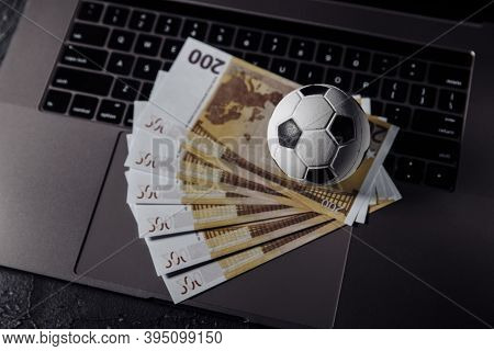 Bets, Sports Betting, Bookmaker. Soccer Ball And Money On A Laptops Keyboard Close-up