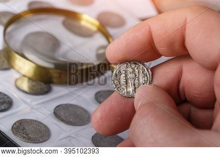 Numismatics. Old Collectible Coins Made Of Silver On A Wooden Table. A Collector Holds An Old Coin.a