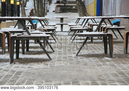 Tables And Benches Covered With Snow Stand On The City Street On A Pavement Next To The Restaurant M