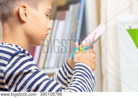 Education, Learning, Paper Craft, Entertainment. Teenage Boy Cutting Colored Paper With Scissors. Ki