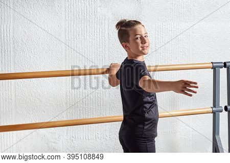 A Beautiful Man Looks Into The Camera And Learns Ballet At A Ballet School.