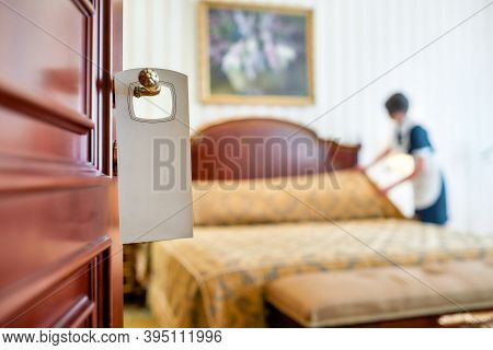A Housemaid In Uniform Cleaning A Hotel Room In The Background And Door With A Sign At The Front. Ro