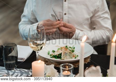 Man Eating Crispy Calamari Salad With Lettuce, Lemon And Asparagus
