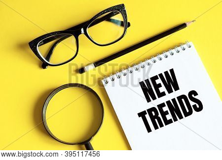 New Trends Text Written On A Notebook With Glasses, Magnifying Glass And Pencil. The Main Tendency I