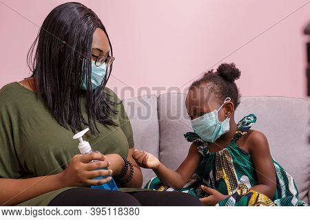 African Americans' Mother And Daughter Wearing A Mask Are Washing Their Hands With Alcohol To Protec