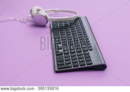 Modern Wireless Keyboard And White Headphones On A Purple Background. Peripheral Devices For The Com