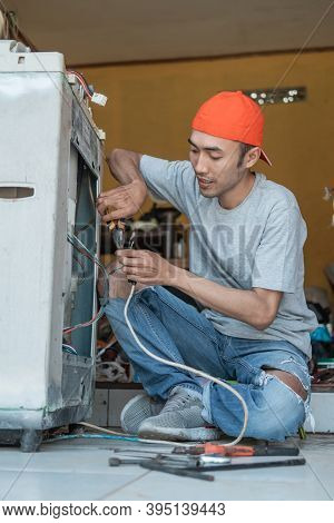 Asian Electronics Workers Use Pliers To Fix A Washing Machine Cable That Broke While Squatting