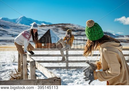 Three Happy Young Girlfriends Are Having Fun At Wooden Fence At Wintertime Outdoors In Mountains. Wi