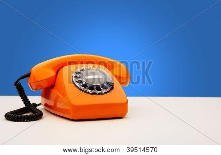 Vintage Orange Telephone On Blue Background