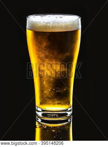 Pint of cold delicous draught beer on black background
