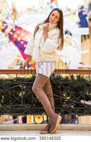 Full length portrait of young woman in white fur coat and high suede boots