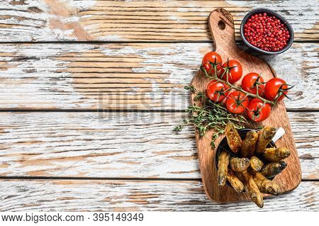 Whole Fried Capelin Fish Served On Cutting Board. White Background. Top View. Copy Space