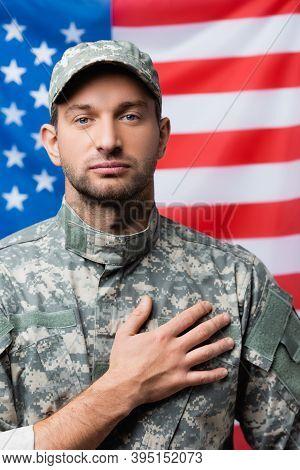 Military Man In Uniform Pledging Allegiance Near American Flag On Blurred Background