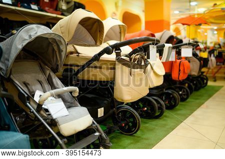 Row of baby strollers in children's store, nobody
