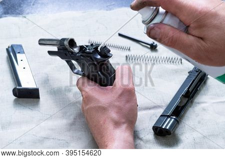 The Gunsmith Lubricates The Mechanism Of The Pistol. Injection Of Lubricating Oil Through A Straw.