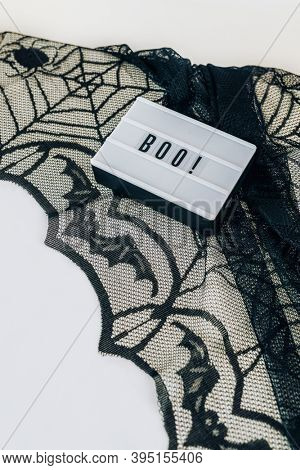 Boo inscription on a white letter board placed on a black lace tablecloth