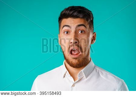 Amazed And Confused Bearded Young Man Looks With Astonishment.