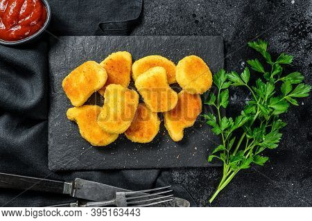 Crispy Homemade Baked Chicken Nuggets. Dark Background. Top View