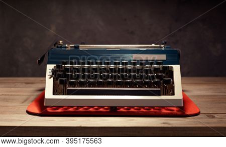 vintage typewriter at wooden top table near wall background surface, screenwriter or retro writer concept