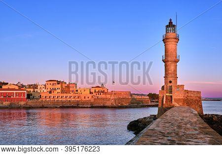 Egyptian Or Venetian Lighthouse Of Old Venetian Harbour Of Chania, Crete, Greece At Sunrise. Soft Sk
