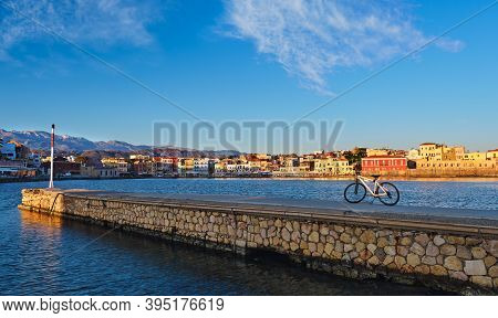 Early Morning In Old Venetian Port Of Chania, Crete, Greece. Pier And Bicycle In Foreground. Quaysid