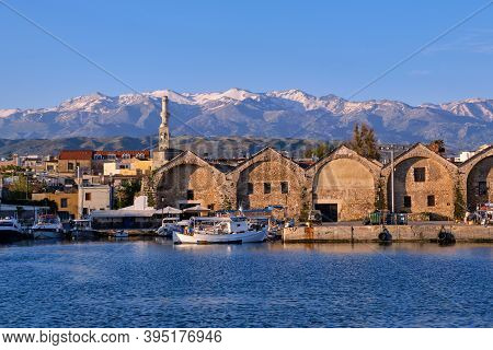 Fishing Boats Anchored By Piers Of Old Venetian Shipyards Or Neoria. Church Bell Tower And Minaret,