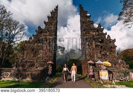 Beautiful Couple At The Baltic Temple. Man And Woman Traveling In Indonesia. Couple At The Bali Gate