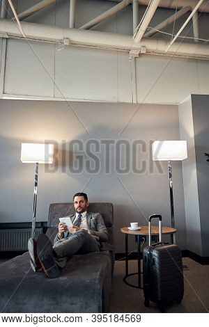 Businessman Reclining On A Bed With A Tablet
