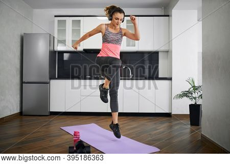 Side View Of Strong Young Woman Jumping On Mat In Kitchen. Fit Girl Wearing Sports Outfit And Headph