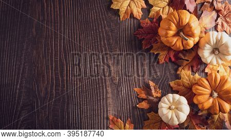 Thanksgiving Background Decoration From Dry Leaves And Pumpkin On Old Wooden Background. Flat Lay, T