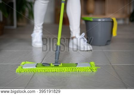 A Professional Cleaner Washes The Floor With A Mop. A Green Rag Rubs The Floor. Cleaning Of Apartmen