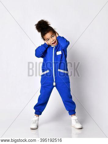 Happy Screaming Loudly Emotional Dark-skinned Kid Girl In Blue Trendy Jumpsuit And White Sneakers Pe